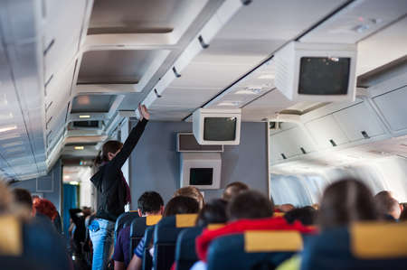puts: girl puts hand baggage on Board the aircraft