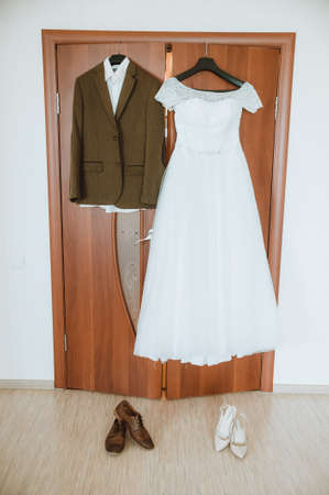 blinder: bride dress and grooms suit on a hanger, hanging in the room on the door