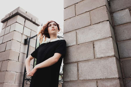 kinky: portrait of a beautiful woman with dark red hair, dressed in black, with a white collar. outside, with natural light. hairstyle and make-up in grunge style Stock Photo