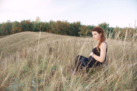 autumn young: Pregnant woman in black dress and dreadlocks on the background of wild nature, autumn, embracing belly.
