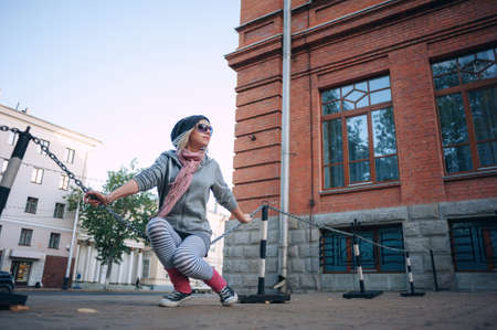 outerwear: Stylish and fashionable girl on a walk around the city. Black and white knitted hat sneakers, pink socks. Outerwear, warm clothing. Fashionista. clothing items. Autumn clothes.