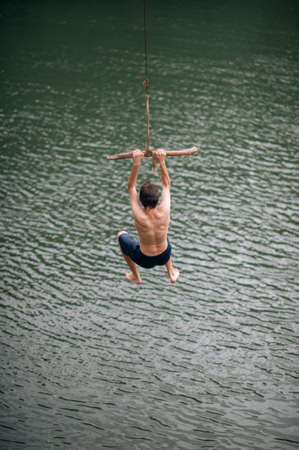 a young man jumping with a rope into the river, outdoors