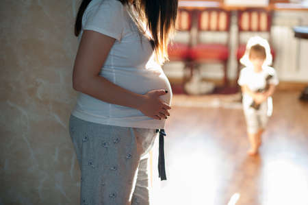 eldest: Pregnant woman standing on the background plays the eldest daughter. at home Stock Photo