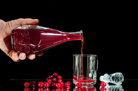 hand man pours red liqueur, cranberry juice,  , isolated on a black background.