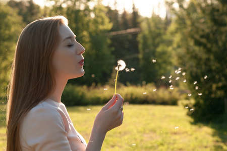 Lovely young girl blowing on a dandelion. Portrait of an outdoor lifestyle Spring annotation