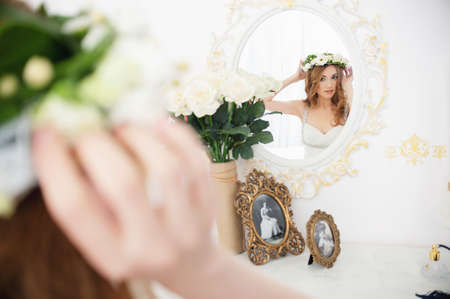 Beautiful girl with brown long hair looking in a mirror trying on a wreath of flowers - Portrait of a young woman in a white room, a boudoir, in a white dress