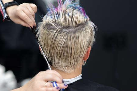 Kapsel voor vrouwen. Kapper, schoonheidssalon. Professionele kapper die modieus kapsel maakt. Kapper snijden vrouw pony haar. Proces van haarknipsel met gebruiksschaar
