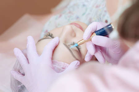 A young woman lies and gets a make-up of her eyebrows in a beauty salon. The use of permanent makeup on the eyebrows. The master works with the eyebrows. Semi-permanent makeup.
