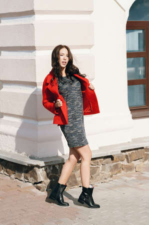 Young beautiful stylish woman dressed in a red coat, gray knitted dress, black boots. Street style, spring and autumn trend, flirty look, hair in the wind