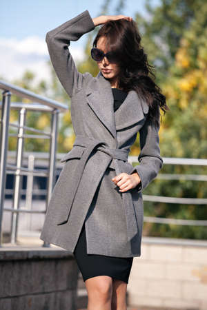 Outdoor portrait of a young beautiful fashionable woman, outdoors. A model dressed in a stylish gray coat, sunglasses. The concept of womens fashion, urban lifestyle Stock Photo
