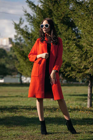 Outdoor portrait of a young beautiful fashionable woman, outdoors. The model, dressed in a stylish orange coat, sunglasses. The concept of womens fashion, urban lifestyle