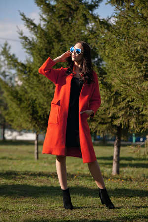 Outdoor portrait of a young beautiful fashionable woman, outdoors. The model, dressed in a stylish orange coat, sunglasses. The concept of womens fashion, urban lifestyle.