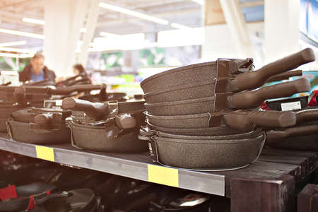 New hang in a row pans in the store. cooking utensils Stock Photo