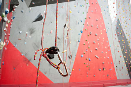 Climbing. A safety bolt threaded a rope with a carbine. Granite wall.