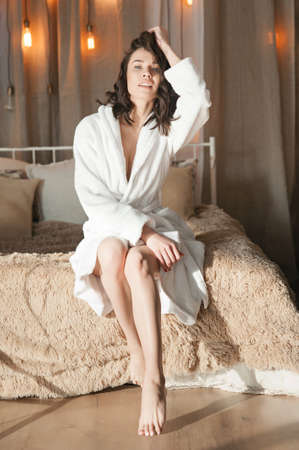 Morning attractive brunette woman in white, homecoming dressing gown sitting on the edge of her bed, after a dream.