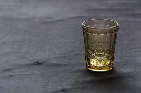 transparent, crystal glass of golden color, on a dark wooden table Reklamní fotografie
