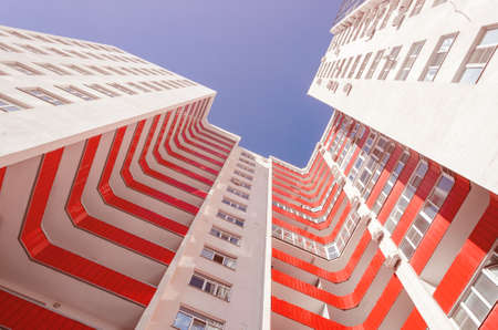 View of a residential building from the bottom up. White house with red balconies in a warm sunny day