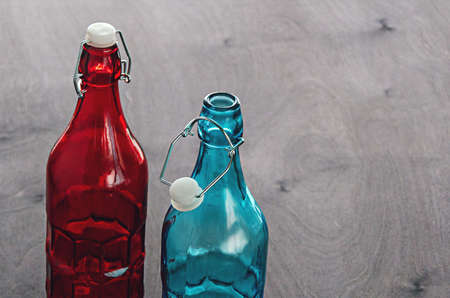Colored bottles, blue and red glass with a cogged stopper on the neck, on a wooden tabletop Reklamní fotografie