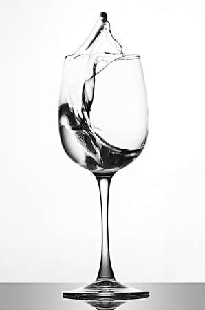 A splash of crystal clear water in a glass for wine. Water splashes. Drinking water. Alcohol Reklamní fotografie