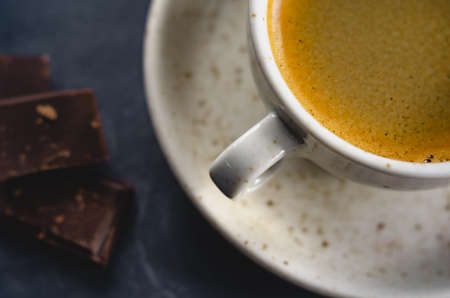 macro photo. light cup of black coffee with chocolate on the rustic table from a height. bokeh