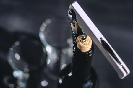 macro photography. Opening a bottle of wine with a lever corkscrew in a restaurant. boke