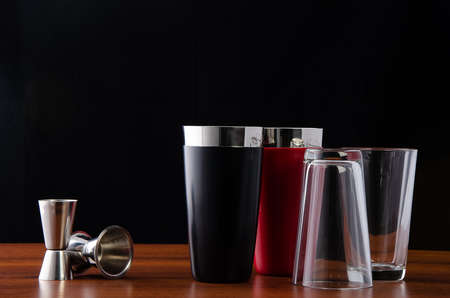 Two Boston shakers, black and red, and two jiggers for making cocktails at the bar. Shaker disassembled: glass cover