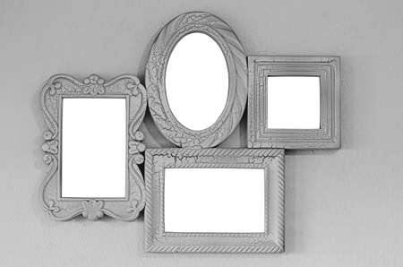 A collage of four empty photo frames on a gray wall, decor layout. Isolated on white background
