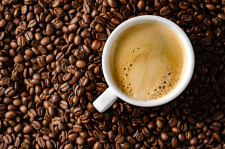 coffee beans background with white cup, copy space