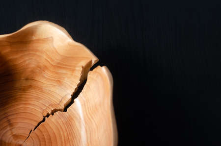 Detail of a simple brown wooden bowl with a crack on the edge on a black wooden background and copy space