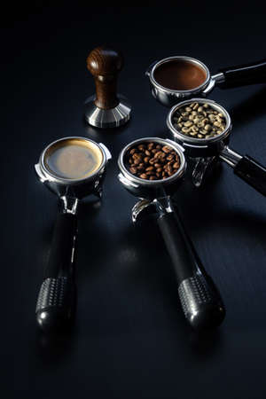Tamper and four espresso filter holders filled with green, roasted, ground beans and ready-made espresso coffee on a black table. Concept. With selective focus. Copy space