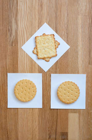 two cookies with filling, and crackers laid out on white stickers, in the form of a house