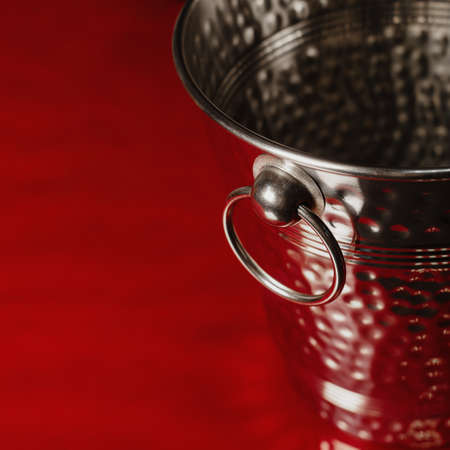 Empty steel bucket for ice, on a red background, with highlights and shadows