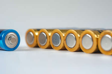 Blue-golden AA batteries close-up on a white background. shallow depth of field, macro