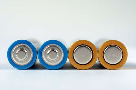 Four blue-golden AA batteries close-up on a white background. shallow depth of field, macro