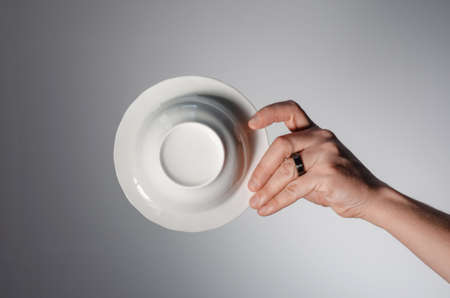 Male hand holding a white plate, on a light background. bottom view