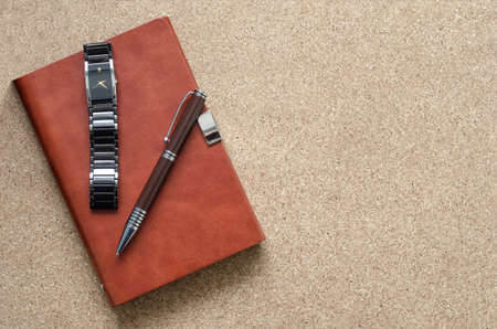 Mens accessories notebook, pen, watch, on a cork background. Work, fashion and style. Business concept. Reklamní fotografie