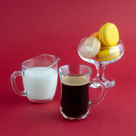 A transparent cup of black coffee and a milkman and a vase with cookies placed on a red surface Фото со стока