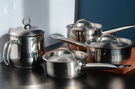 Stainless steel pots and utensils on table counter 免版税图像