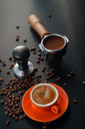 Tempera, holder, and orange barista cup with espresso. Equipment for making freshly brewed coffee