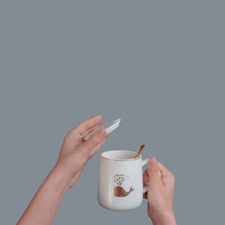 White cup with a spoon in the hand of a teenager, on an isolated gray background 스톡 콘텐츠