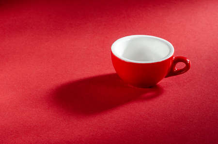 Red mug on a red background for your design. Promotional photo