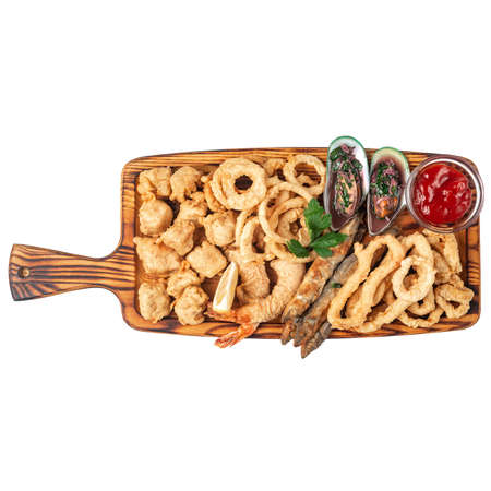 Fried fish, onion rings, batter shrimps, mussels in sauce on a wooden board for serving. Isolate