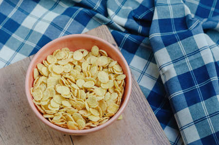Cornflakes in a pink bowl, on a wooden table. copy space