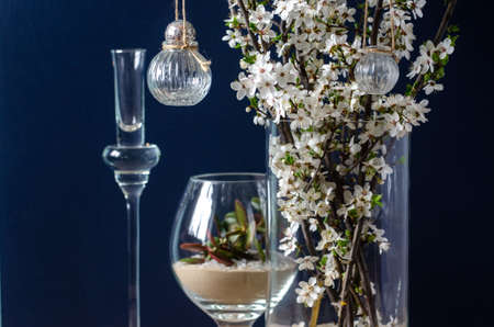Original wedding flower decorations in the form of mini-vases and bouquets of flowers, hanging on a flowering branch 스톡 콘텐츠