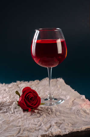 a glass of rose wine with a rose