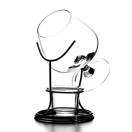 Isolated objects: a small single empty classic cognac glass, on a metal stand, on a white background