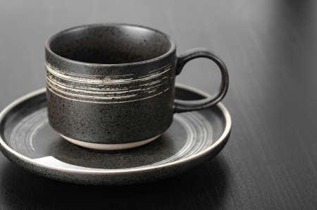 Gray cup and saucer on a black table. Close up with shallow depth of field