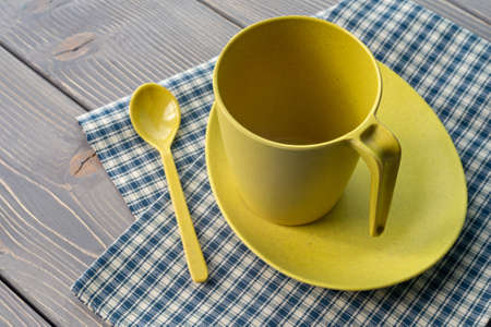 Yellow cup on a saucer with a spoon. Utensils of bamboo, with a checkered napkin on a wooden table. Shallow depth of field
