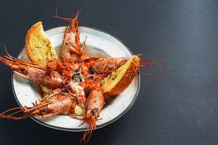 dishes with langoustines, in a plate on a black background. view from above. copyspace.