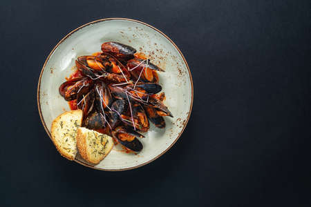 dishes with mussels in a plate on a black background. view from above. copyspace. seafood